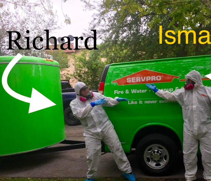 Employees in white protective suits pointing at each other in front of two green SERVPRO vans.