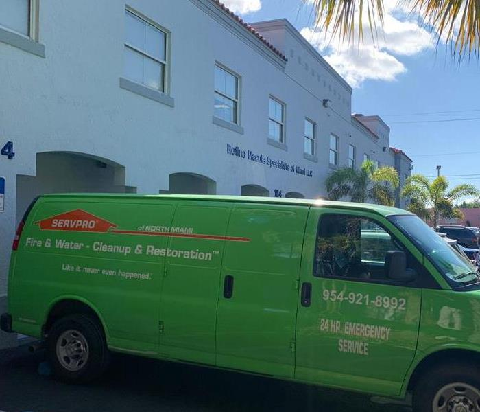SERVPRO green van parked outside a building.