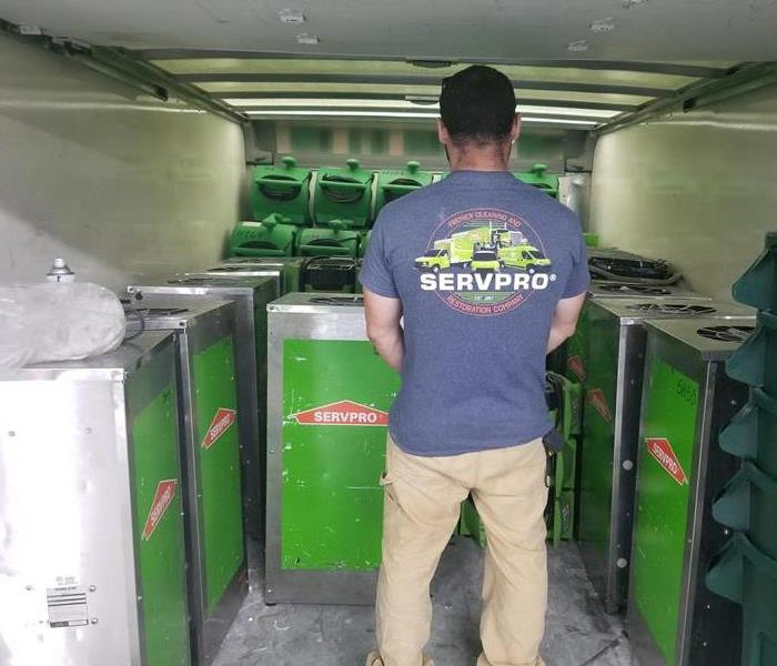 Employee standing in the bed of a SERVPRO green truck checking stock.