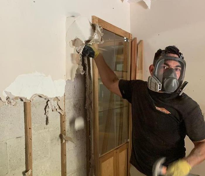 Employee in a protective mask breaking down drywall.