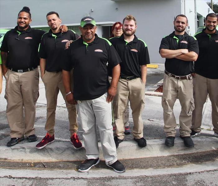 Crew photo, employees are in a row wearing black polos.