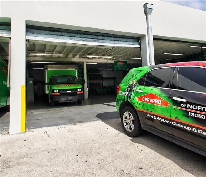 Garage with a green SERVPRO truck inside, and one outside.