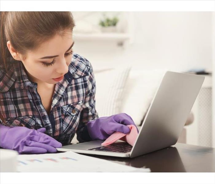 Woman cleaning laptop keyboard.